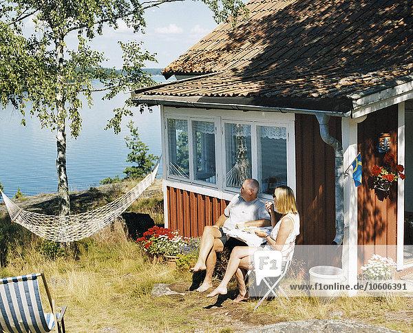 Außenaufnahme, sitzend, Wohnhaus, Meer, rot, Kaffee, Mann und Frau