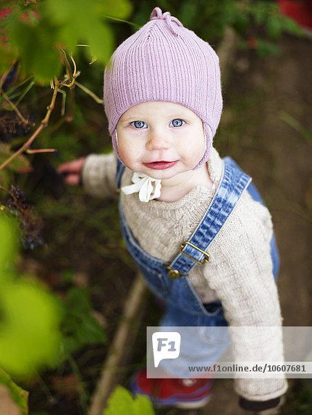 A happy little girl in a garden  Sweden.