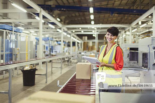 Portrait lächelnder Arbeiter beim Kontrollieren von Kartons auf der Förderband-Produktionslinie in der Fabrik