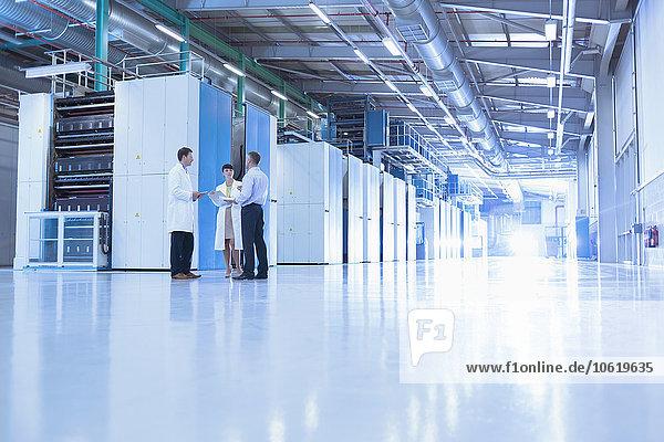 Wissenschaftler und Geschäftsleute im Gespräch in der Fabrik