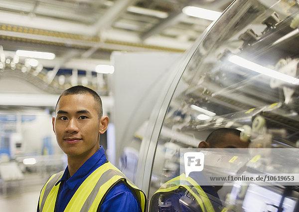 Porträt eines selbstbewussten Arbeiters  der sich auf Maschinen in der Fabrik stützt.