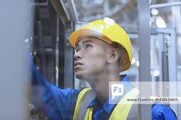 Arbeiter in einer Maschinenfabrik  die sich mit harten Hüten beschäftigt
