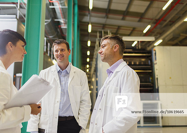 Wissenschaftler und Geschäftsfrau im Gespräch in der Fabrik