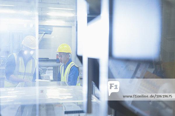 Arbeiter im Gespräch an Maschinen in der Fabrik