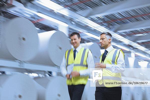 Geschäftsleute in reflektierender Kleidung  die in der Druckerei an großen Papierrollen entlanggehen