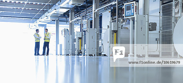 Arbeiter im Gespräch mit Maschinen in der Fabrik