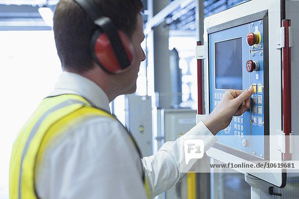 Arbeiter mit Gehörschutz am Bedienpult der Maschine