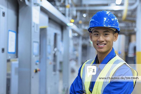 Porträt eines lächelnden Arbeiters mit Helm in der Fabrik