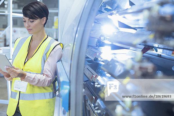 Arbeiter mit digitalem Tablett auf Maschinen in der Fabrik
