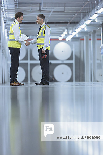 Geschäftsleute in reflektierender Kleidung schütteln sich die Hände in der Druckerei.