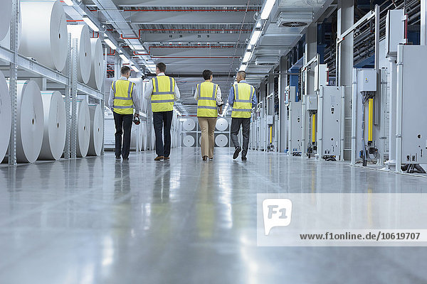 Arbeiter in reflektierender Kleidung gehen in der Druckerei an großen Papierrollen vorbei.