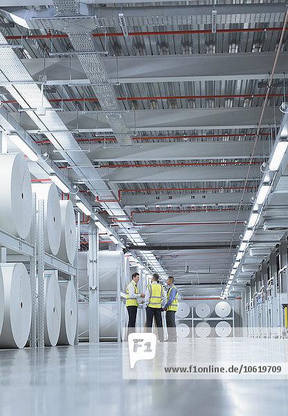 Arbeiter in reflektierender Kleidung reden in der Nähe von großen Papierrollen in der Druckerei