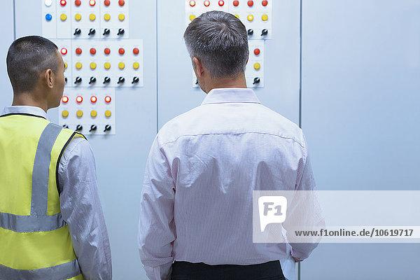 Supervisor und Mitarbeiter am Schaltschrank in der Fabrik