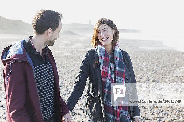 Lächelndes Paar beim Spaziergang am Strand