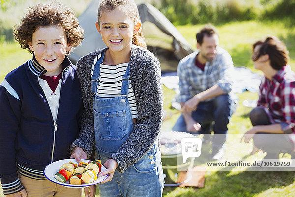 Portrait lächelnde Geschwister mit Gemüsespießen auf dem Campingplatz