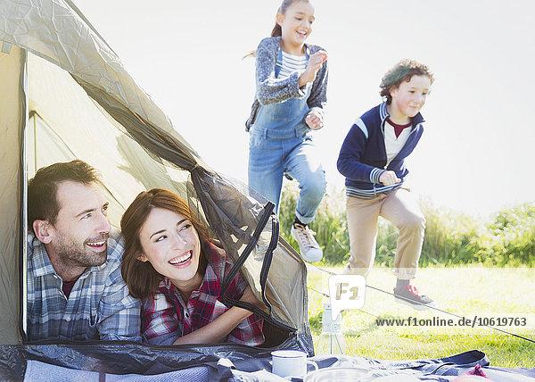 Lächelndes Paar im Zelt  das Kinder beim Laufen im Gras beobachtet