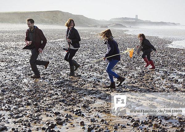 Familienlauf am felsigen Strand