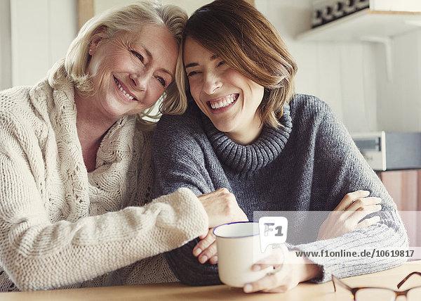Lachende Mutter und Tochter in Pullovern umarmend und Kaffee trinkend