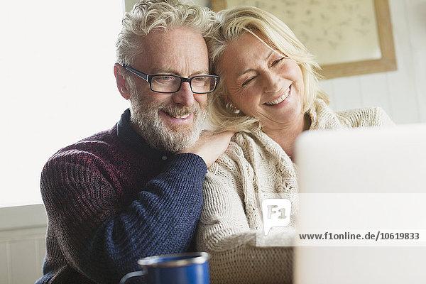 Lächelndes Seniorenpaar mit Laptop in der Küche