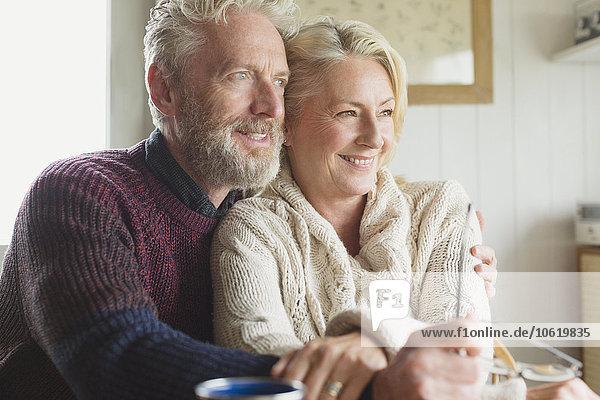 Lächelndes Seniorenpaar umarmt und wegblickend