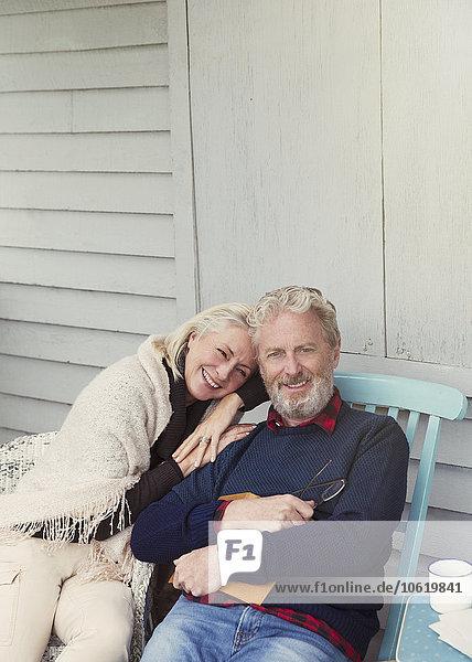 Portrait lächelndes Seniorenpaar  das sich auf der Terrasse umarmt