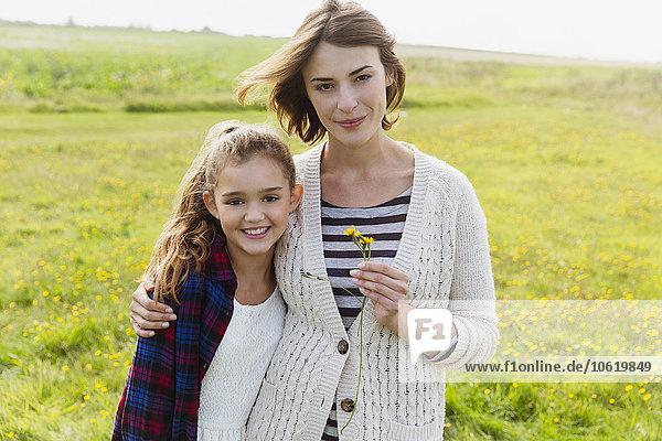 Portrait lächelnde Mutter und Tochter auf Wiese mit Wildblumen