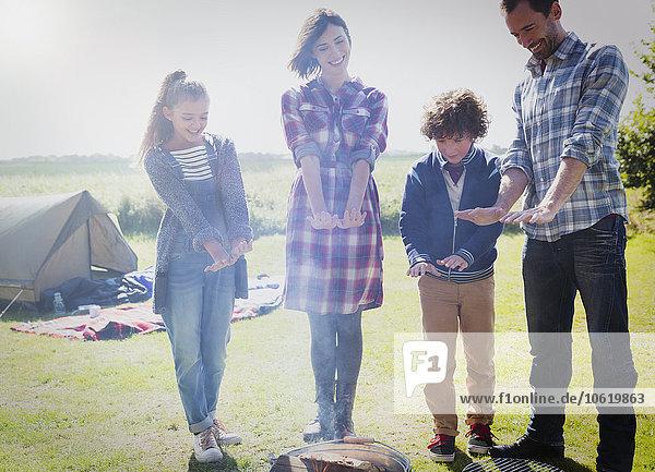 Family warming hands at campfire