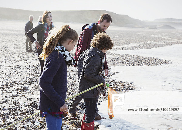 Multi-generation family clamming on rocky beach