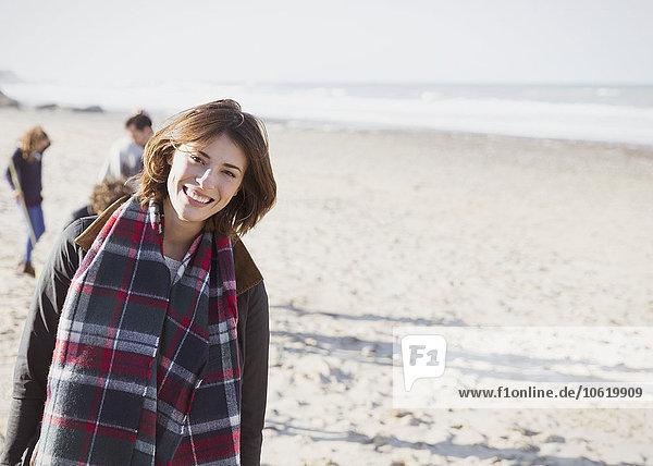 Portrait lächelnde Frau im karierten Schal am sonnigen Strand