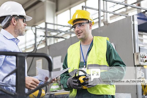 Ingenieur und Arbeiter in Arbeitsschutzkleidung im Gespräch in der Fabrik