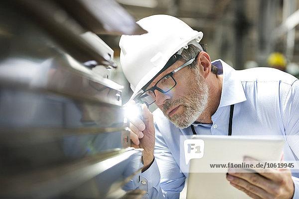 Fokussierter Ingenieur mit digitalem Tablett und Taschenlampen-Untersuchungsteil im Werk