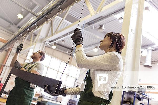 Arbeiter hängen Stahlteil in der Fabrik auf