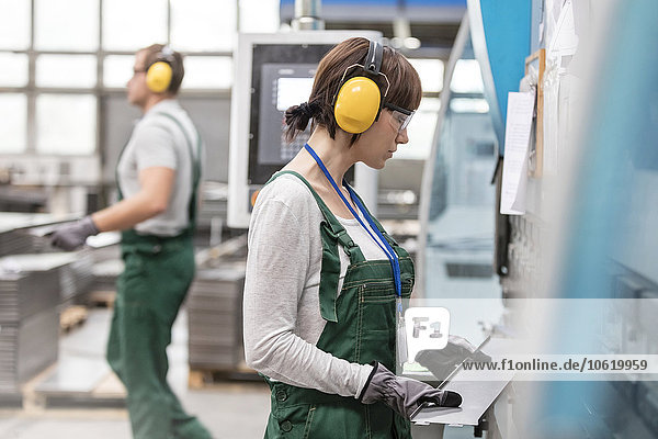 Arbeiterin mit Gehörschutz  die das Metallteil in der Fabrik hält