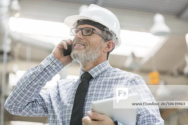 Ingenieur mit Hard-Hut und digitalem Tablett am Handy