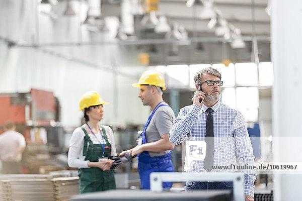 Geschäftsmann und Arbeiter in der Fabrik