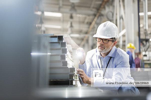 Ingenieur beim Prüfen von Stahlteilen mit Taschenlampe im Werk
