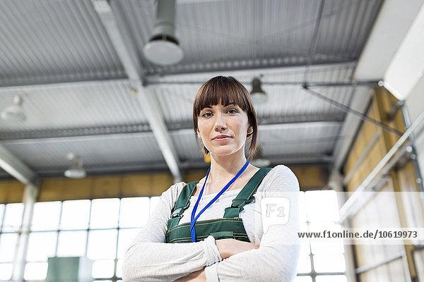 Porträt ernsthafte Arbeiterin mit gekreuzten Armen in der Fabrik