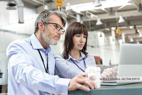 Geschäftsleute mit Kaffee am Laptop in der Fabrik