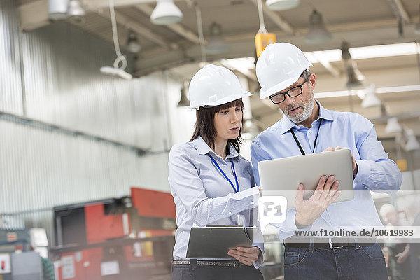 Ingenieure mit Laptop in der Fabrik