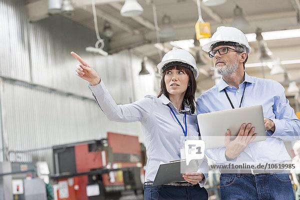 Ingenieure mit Laptop und Zwischenablage im Werk