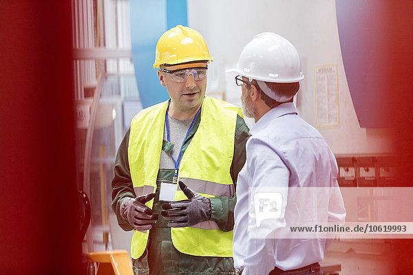 Ingenieur und Arbeiter im Gespräch in der Fabrik