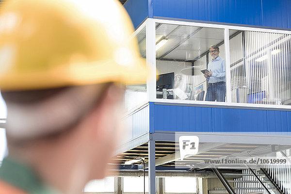 Arbeiter schaut zum Geschäftsmann in der Fabrik auf
