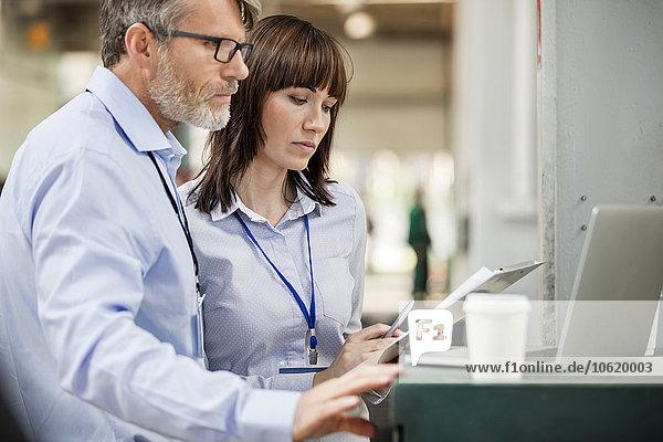 Geschäftsleute mit Zwischenablage arbeiten am Laptop in der Fabrik