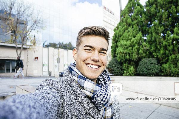 Portrait of smiling teenage boy taking a selfie
