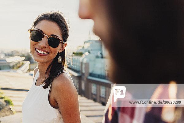 Österreich  Wien  Porträt einer lächelnden jungen Frau mit Sonnenbrille  die auf einer Dachterrasse flirtet.