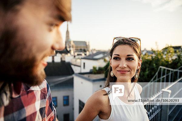 Österreich  Wien  Porträt einer lächelnden jungen Frau von Angesicht zu Angesicht mit ihrem Freund auf einer Dachterrasse