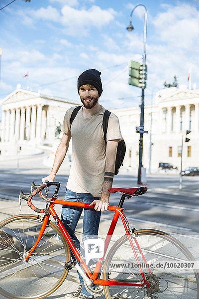 Junger Mann mit Rennrad in Wien  vor dem Parlamentsgebäude  Dr.-Karl-Renner-Ring