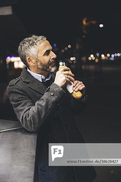 Österreich  Wien  Mann mit Käse Carniolan Wurst am Wurststand bei Nacht