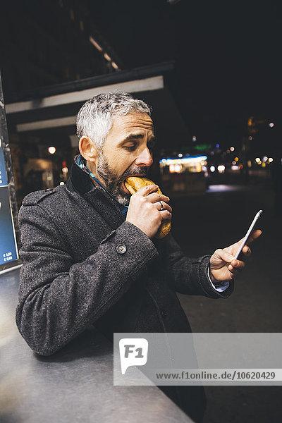 Österreich  Wien  Mann isst Käse Carniolan Wurst beim Anblick des Smartphones bei Nacht