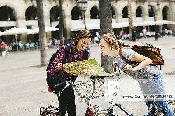 Spanien  Barcelona  zwei glückliche junge Frauen mit Karte auf Fahrrädern in der Stadt